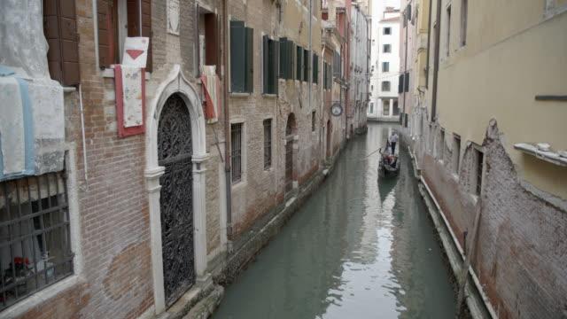 gondola down a narrow canal / venice, italy - れんが造りの家点の映像素材/bロール