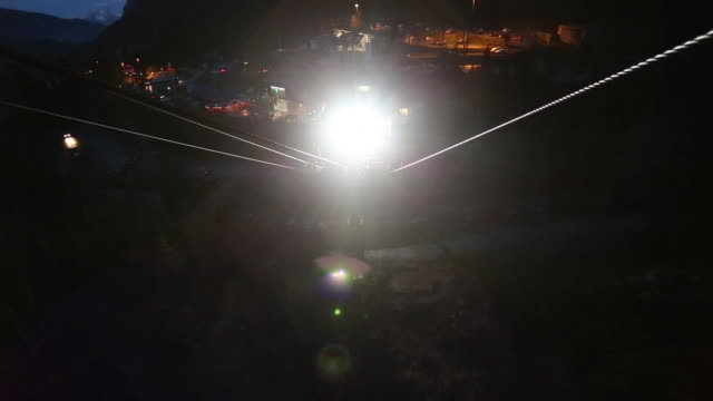 A gondola lift on the way down to the ski resort at nighttime. - filmed in Kaprun, Austria, Europe