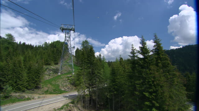 vídeos de stock e filmes b-roll de a gondola lift tower comes into view as a cable car travels to the dolomites in italy. - cable
