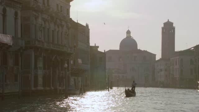 WS POV Gondola moving in Venice's Grand Canal, San Geremia, Church background / Venice, Italy
