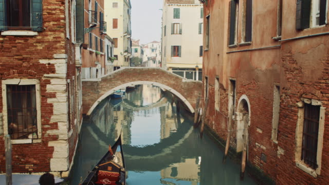 ws - gondola passing under a typical venetian bridge - standbildaufnahme stock-videos und b-roll-filmmaterial