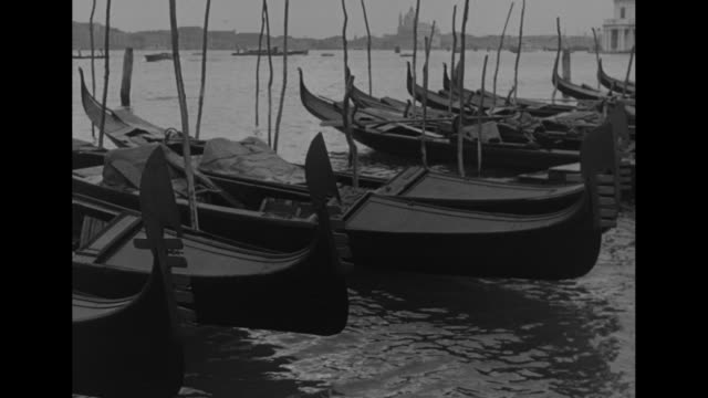 gondolas anchored in foreground, cathedral of san giorgio maggiore in bkgd, across water / gondolas, other boats and cathedral in bkgd / tilt up lamp... - anchored stock videos & royalty-free footage