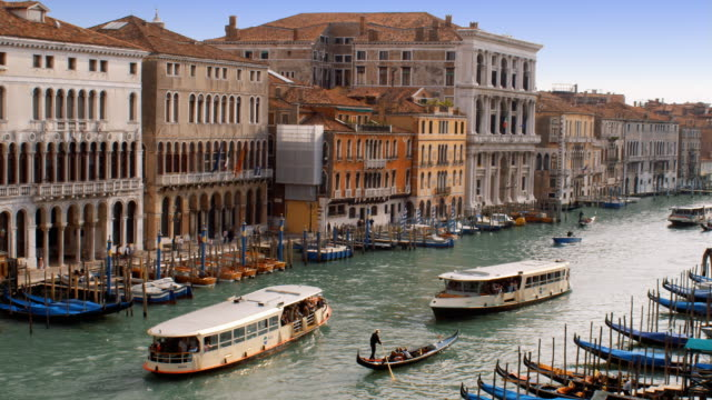 gondolas and water buses cruise along the grand canal in venice, italy. - grand canal venice stock videos & royalty-free footage