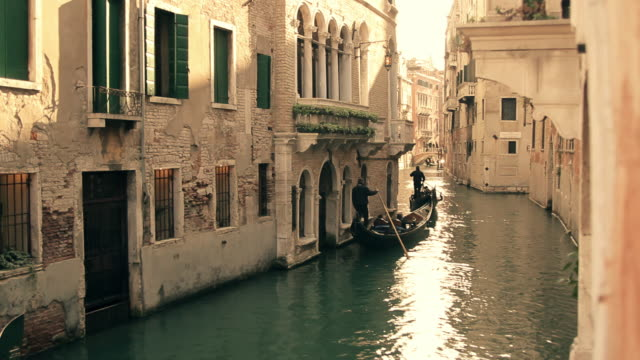 gondolas at sunset in canal, venice, veneto, italy - 史跡めぐり点の映像素材/bロール