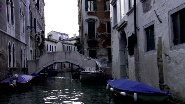 vídeos de stock, filmes e b-roll de gondolas dock alongside waterfront buildings in venice's ghettos. available in hd. - gueto