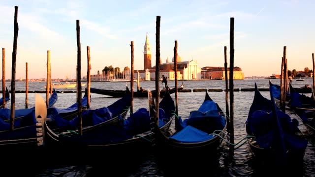 gondolas moor in a lagoon at sunset before the san giorgio maggiorl island in venice. - vagare senza meta video stock e b–roll