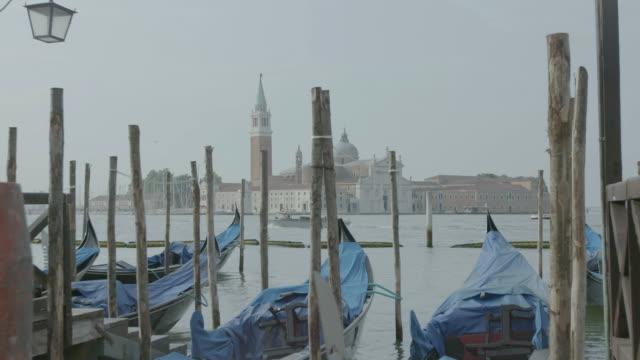WS Gondolas moored at Grand Canal, Church of San Giorgio Maggiore seen in background / Venice, Italy