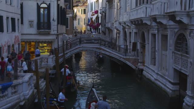 Gondolas move through a small canal in Venice, Italy.