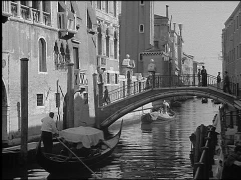 B/W 1930 gondolier driving gondola on narrow canal toward footbridge / Venice, Italy