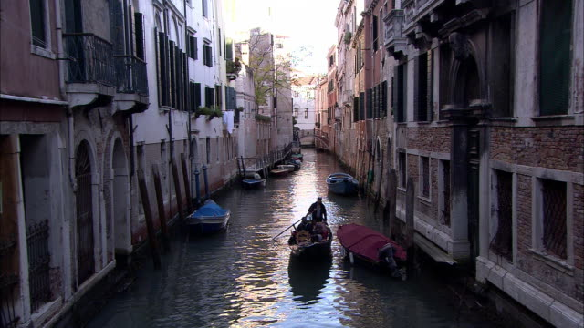 A gondolier guides his gondola along a canal in Venice.