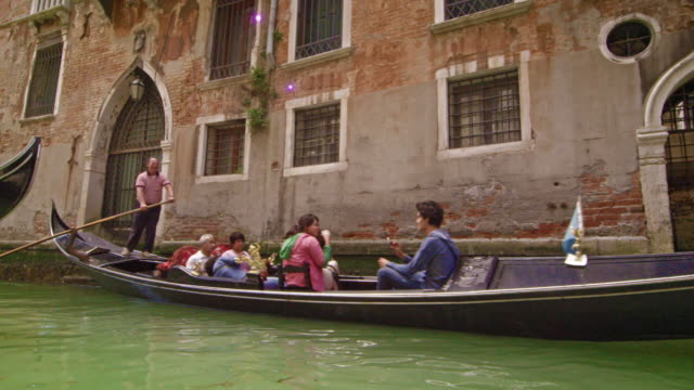 Gondolier guiding boat down canal in slow motion