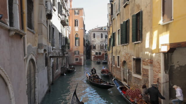 A gondolier maneuvers his boat through a narrow canal.