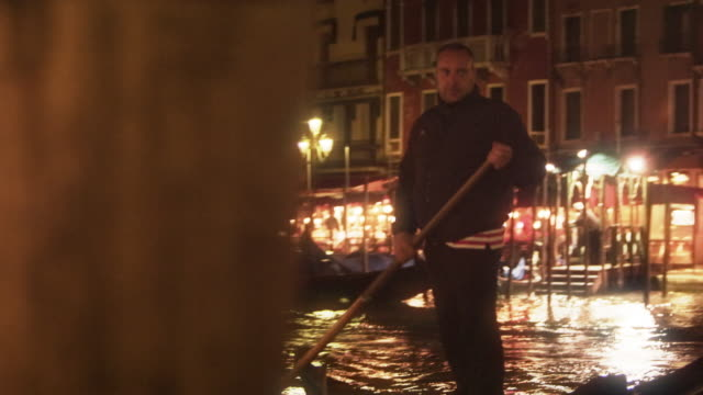 a gondolier paddles his boat on the grand canal at night - italian currency stock videos & royalty-free footage