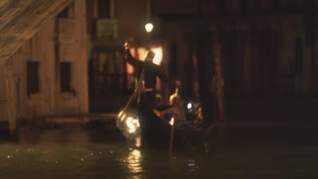 Gondolier paddling boat at night