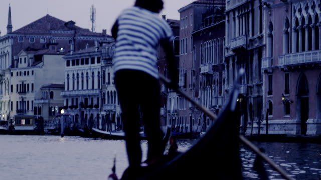 A gondolier rides his gondola in a canal in Venice