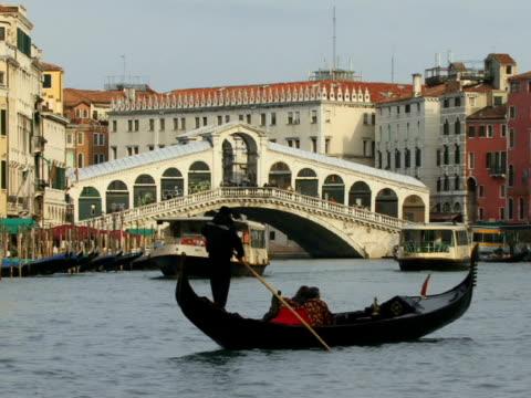 WS Gondolier rowing gondola near Rialto Bridge on Grand Canal near tour boats / Venice, Italy