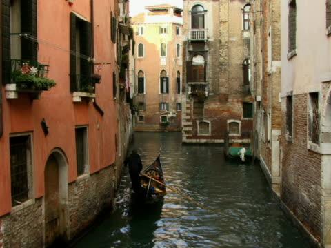 HA WS Gondolier rowing gondola on canal past buildings / Venice, Italy