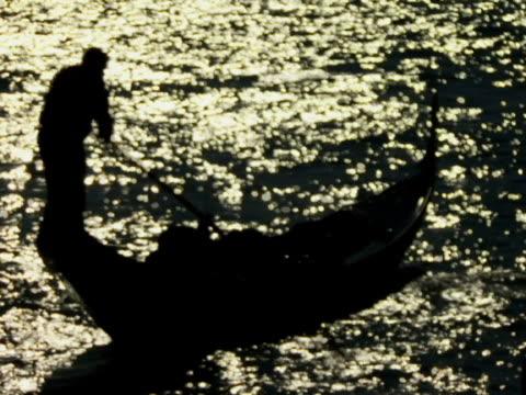 HA WS Gondolier rowing gondola on canal reflecting sunlight / Venice, Italy