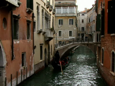 WS Gondolier rowing gondola toward footbridge on canal / Venice, Italy