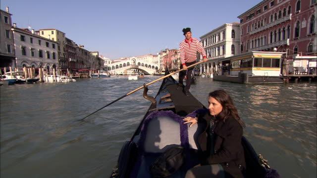 A gondolier rows a gondola through a canal in Venice, Italy.