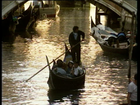 Gondolier sails Gondola full of passengers zoom out along wide Venetian canal towards Bridge of Sighs busy bridge with people in background sun reflecting off of water Venice