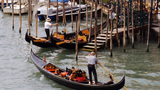 A gondolier steers a gondola away from a dock on the Grand Canal in Venice, Italy.