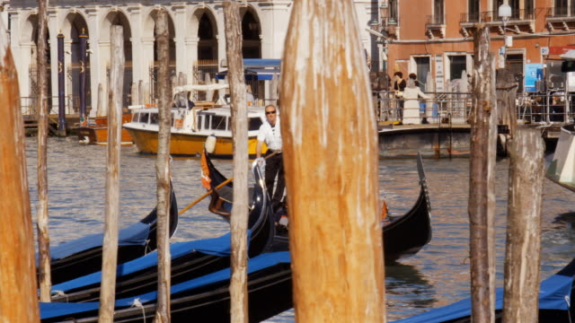 A gondolier steers a gondola past other boats on Grand Canal in Venice, Italy.