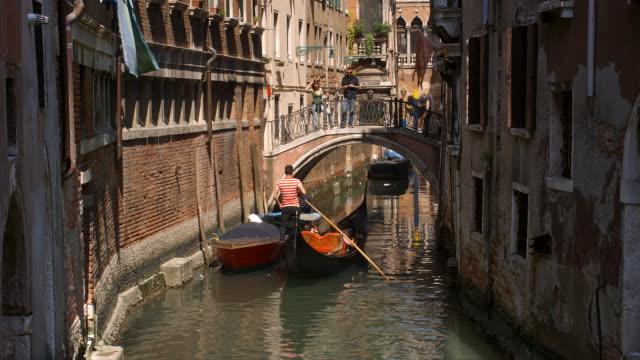 A gondolier takes tourists on a ride down the Rio della Verona canal and under the Calle della Verona bridge in Venice, Italy.