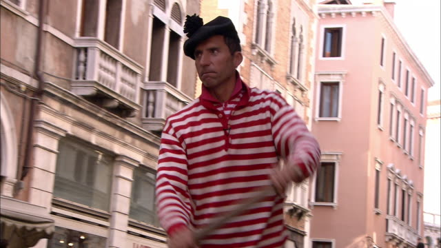 A gondolier wears a red and white striped shirt and a beret with a small pom-pom on the top.