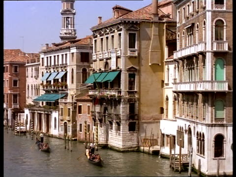 gondoliers steer their boats through the grand canal in venice, italy. - grand canal venice stock videos & royalty-free footage