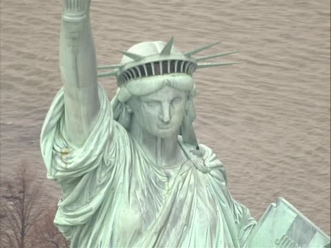 good aerial stock shot overhead of statue of liberty, starts on to slight zoom out and push back in to head and body with nice park and american flag... - war in afghanistan: 2001 present stock videos & royalty-free footage