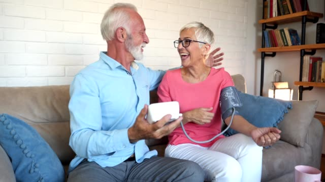 vídeos de stock e filmes b-roll de good and healthy news for a senior couple measuring blood pressure - medidor de tensão arterial