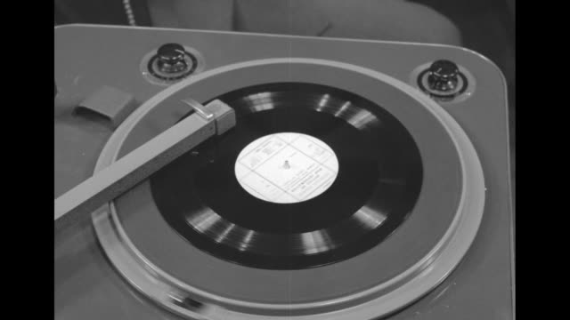 good footage of a young radio broadcaster in control room of facility with angled control panels around him and turntables in foreground he places lp... - radio stock videos & royalty-free footage