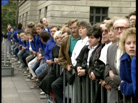 Good general views and close ups of crowds of people and soldiers lining street waiting for Mikhail Gorbachev to arrive on visit to East Berlin for...