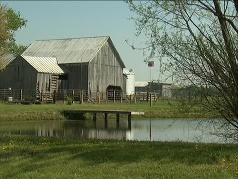 vidéos et rushes de good generic b-roll of a grey barn near a lake good generic stock shot country farm b-roll - étang