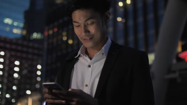 vídeos de stock e filmes b-roll de good looking asian businessman using phone at night after work - 30 34 years