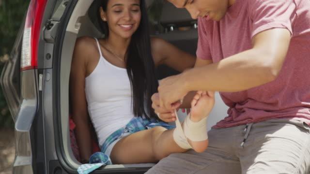 Good looking hispanic man helping injured girlfriend