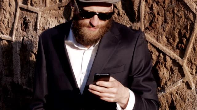 Gut aussehende Mann mit Bart, mit seinem smartphone.