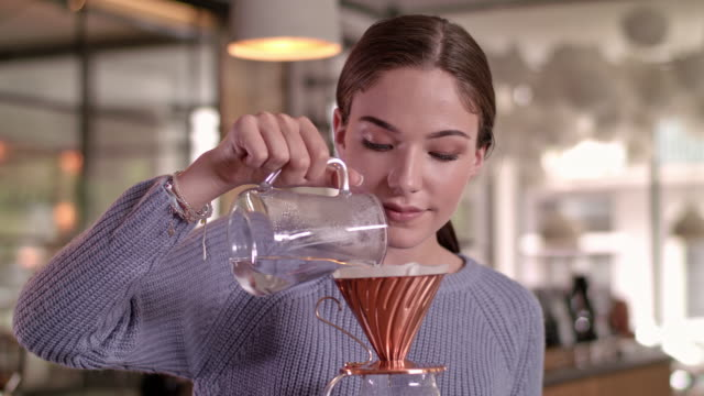 good looking waitress pouring hot water into classic coffee filter in a coffee roasting studio