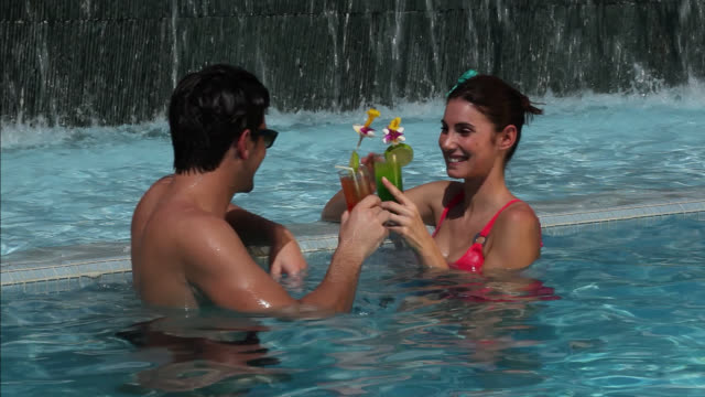 Good Looking Young Couple in the swimming-pool drinking cocktails