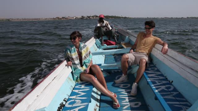 good looking young couple on boat - セネガル点の映像素材/bロール