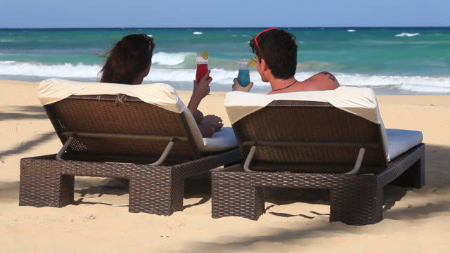 good looking young couple relax by the sea with cocktails - young couple stock videos & royalty-free footage