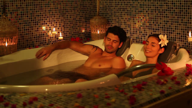 Good Looking Young Couple relaxing in jacuzzi