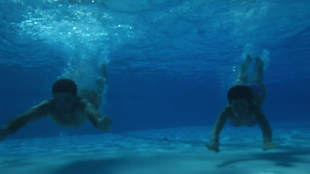 Good Looking Young Couple swimming underwater in pool
