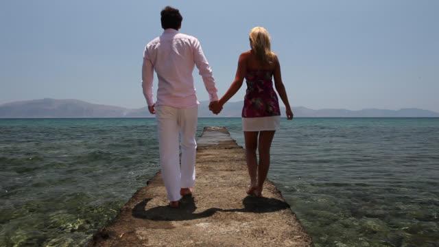 vídeos de stock, filmes e b-roll de good looking young couple walking by the mediterranean - cabelo louro