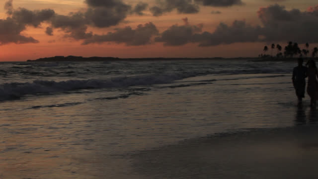 good looking young couple walking by the sea at sunset - punta cana stock videos and b-roll footage