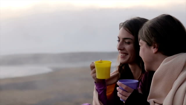 good morning! two girls drinking tea and warming up near beautiful foggy lake - tea cup stock videos and b-roll footage