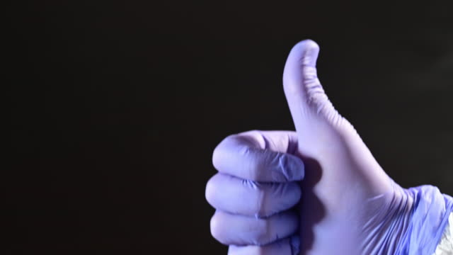 good news. scientist's hand in lab with protective gloves with thumbs up. - glove stock videos & royalty-free footage