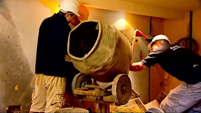int good shots construction workers using cementmixer construction worker on scaffolding lifting steel girder - cement mixer stock videos and b-roll footage