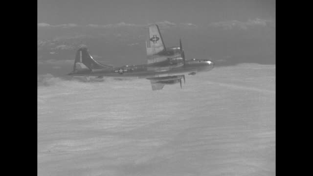 VS good shots of Boeing B29 Superfortress bomber flying in sky amongst clouds during World War II / Note exact day not known